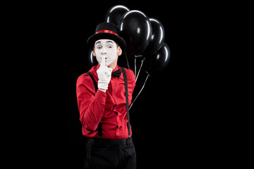 mime holding balloons and showing silence sign isolated on black