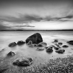 Sonnenuntergang am Greifswalder Bodden, Findlinge am Strand, Ostsee, Insel Rügen, Deutschland, schwarz-weiß