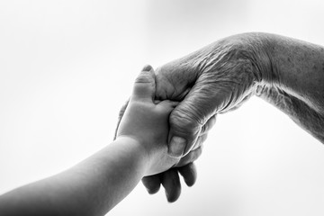 Kind und alte Frau halten die Hand