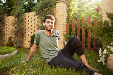 Outdoors portrait of young attractive bearded caucasian male gardener smiling, sitting on grass in garden, enjoying moments of piecsl summer evenings.