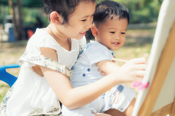 Asian little boy and sister draw together in park. Kids painting and drawing. Children paint with paintbrush color and pencils. Art and crafts for toddler and preschooler..