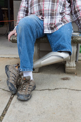 Leg amputee sitting on bench with hands by sides, legs crossed, copy space, vertical aspect