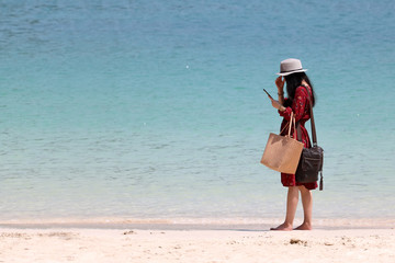 Tourist girl wearing asian style fashion clothes enjoy smart phone on the beach
