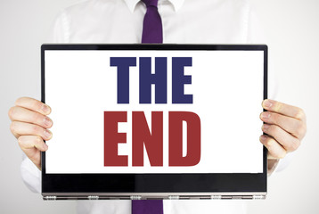 Word, writing The End. Business concept for End Finish Close Written on tablet laptop holding by the man blurred background. Businessman fingers keeping the computer.