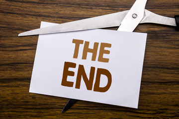 Hand writing text caption inspiration showing The End. Business concept for End Finish Close Written on note, wooden back with colourful scissors meaning destroy stop of something.