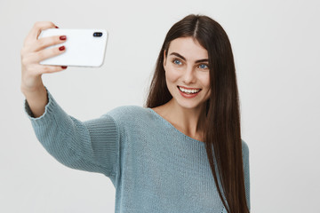 Studio portrait of attractive happy girl taking selfie with new smartphone, smiling brightly while standing over gray background. Woman records her blog to post it in social media