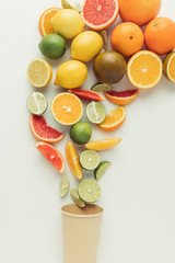 Juicy citruses and paper cup isolated on white background