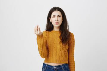 Portrait of disappointed frowning caucasian woman showing italian what do you want gesture, being angry or irritated, standing over gray background. Girl is annoyed of boyfriend jealousy