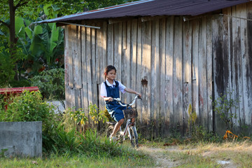 Asian students girl wearing school uniform, enjoy a bicycle in local village in the evening