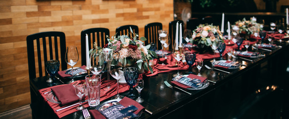 Wedding Banquet with red table setting decoration. Red tablecloth, white dishes, silver cutlery and red fresh flowers