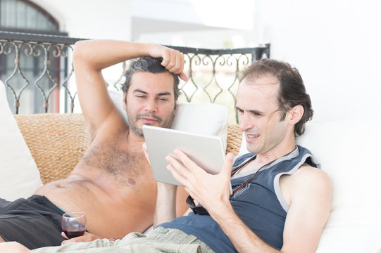 Two casual young man using tablet laying on the sofa in a balcony on a sunny day