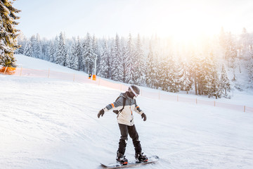 Landscape view on the snowy mountains with slopes and snowboarder riding during the sunny weather