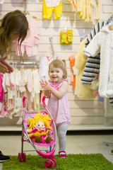 Little cute blue-eyed blonde girl clapping her hands in the kids' store with the toy baby carriage