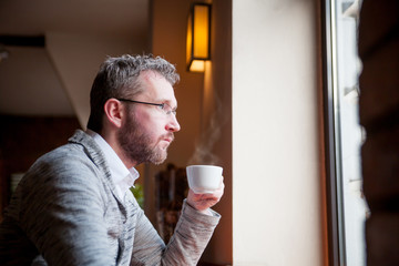 Thoughtful man drinking coffee in cafe and looking out window