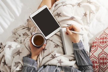 Bed is my office. High angle shot of girl lying in cozy atmosphere, listening music in earphones, holding tablet and drinking tea while making notes in her note pad. Creative girl tries make new poem