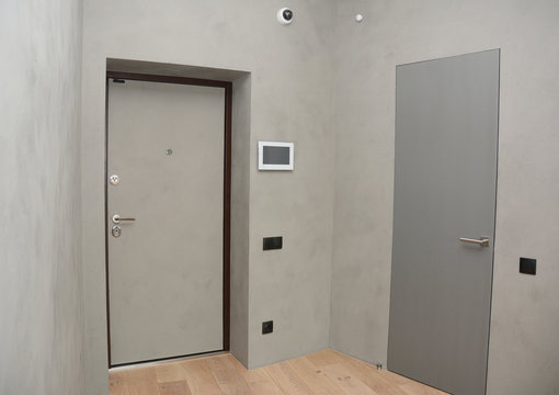 Modern house entrance metal door interior with security  CCTV camera is mounted on the room wall with fire alarm system, smart house system, fire detection and smoke slarm.