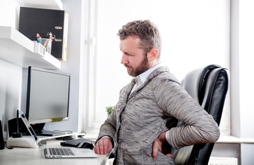 Man in office suffering from back pain