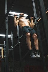 Muscular man practicing pull up on a pull up bar