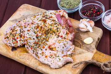 Turkey meat with spices and herbs on cutting board