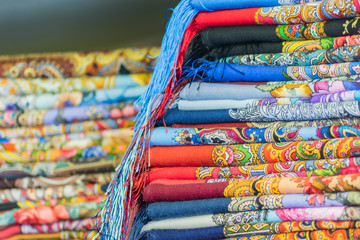 Pile of traditional Russian colorfull scarfs and headscarfs in market. Popular souvenir from Russia