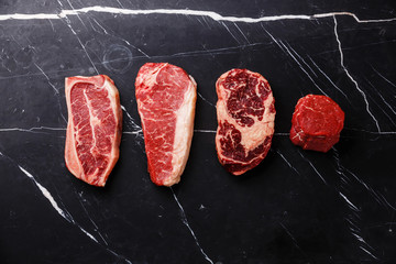 Variety of Raw Black Angus Prime meat steaks Blade on bone, Striploin, Rib eye, Tenderloin fillet mignon on dark marble background copy space