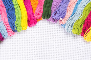 Colored thread for embroidery on white canvas. Copy spase.