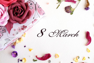 postcard to the international women's day, March 8, from dried flowers and a gift box with three roses