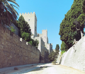 rhodes castle view of walls battlements and towers taken from the dry moat with blue sky