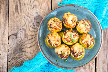 Zucchini stuffed with meat and cheese on blue plate