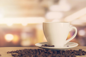 cup of coffee on wooden table with defocus bokeh of coffee shop background. Image with soft focus and blurred background.