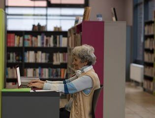 Senior woman using laptop in library