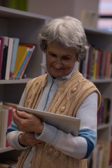Senior woman using digital tablet in library