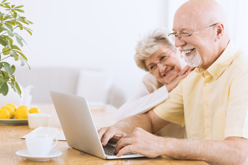 Smiling elderly man searching informations