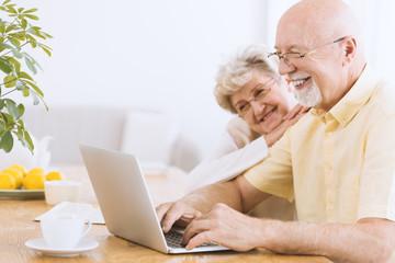 Smiling elderly man searching informations