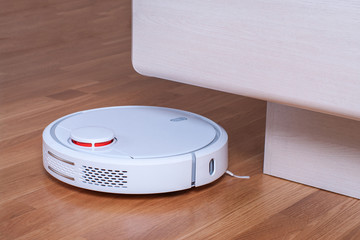 White robot vacuum cleaner runs in bedroom