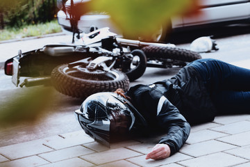 Woman motorcyclist lying unconscious Wall mural