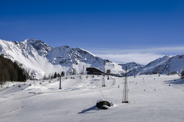 Unidentifiable skiers at ski resort in Pila, Valle d'Aosta, Italy with chairlift and mountain backdrop and copy space