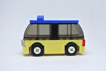 Selected focused of toy bus made from plastic brick and isolated on white background.