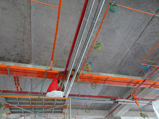 Construction workers installing electrical cable tray and doing wiring works at the construction site.
