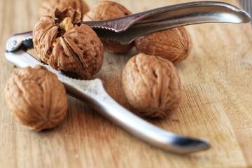 Walnuts and nutcracker on wooden board
