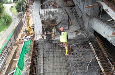 Concreting work by construction workers at the construction site. Wet concrete poured  inside timber form work.