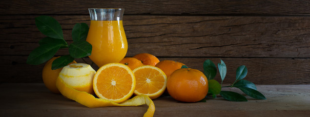 Fresh oranges with green leaf and juice in glass on wooden plate and wooden wall background