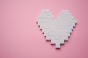 Heart made of cubes of sugar. Sugar kills. Pink background.