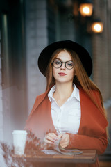 Beautiful girl with Hat and glasses with coffee and a magazine