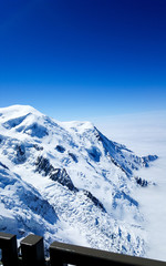 A view from the peak of of Mont Blanc mountain with a blue sky