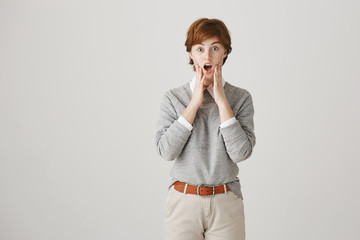 Portrait of amazed or shocked cute redhead woman with short haircut and freckles holding hands on chin, standing with opened mouth, being afraid and confused with what happening over gray background