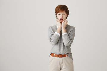 Fear concept. Cute boyish redhead with freckles standing with terrified look and hands over face, staring with fright at camera over gray background. Oh my, there is huge disgusting warm on wall