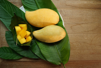 Two yellow mango with already slice in green leaves basket placed on golden teak table