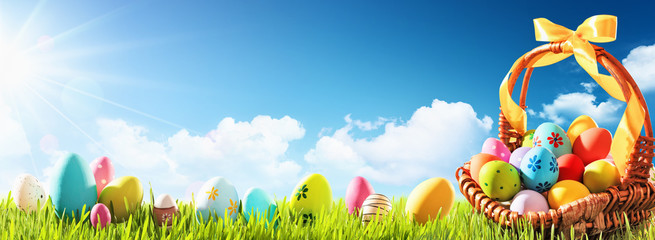 Easter Eggs in a Basket on Green Grass and Blue Sunny Sky