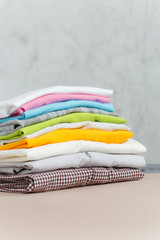 Close up pile of ironing colorful clothes, washed laundry, family clothing on ironing board isolated on white background. Housekeeping concept. Copy space for advertisement. With place for text.